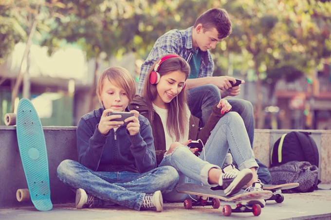 Three teenagers with phones outdoors